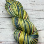 A twisted skein of sock yarn in yellows and blues with hints of pink.