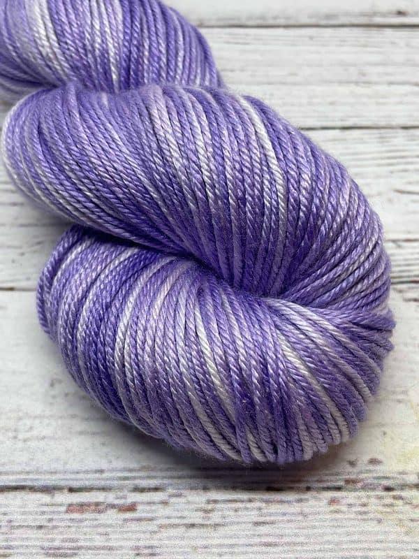 Close up view of tonal light purple and white yarn.