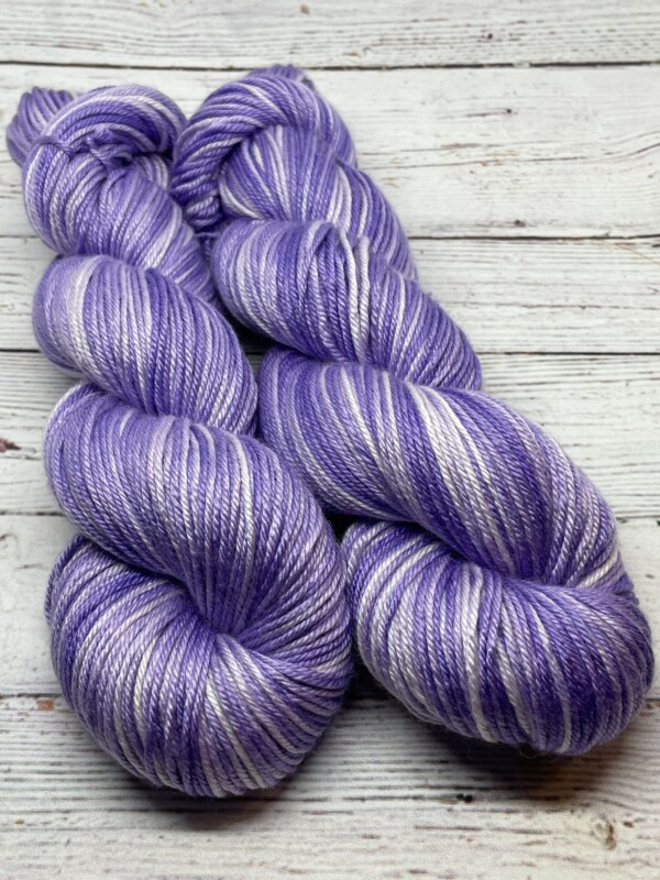 Tow skeins of tonal light purple and white yarn.