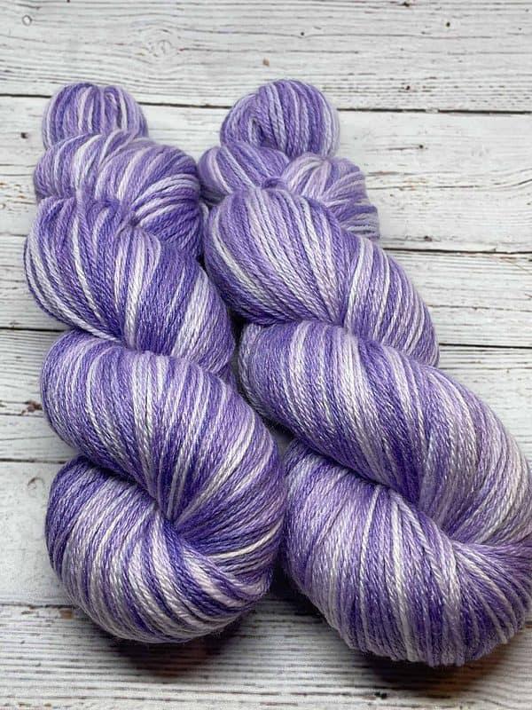 Two skeins of tonal light purple sock yarn.