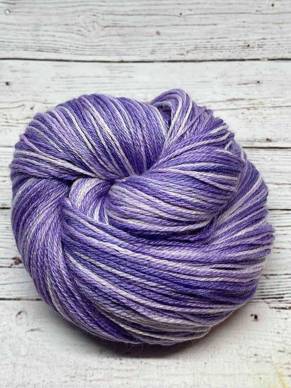 A skein of tonal light purple sock yarn wrapped into a snail shape.